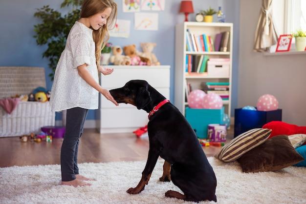 Bambina che gioca con il cane a casa Foto Gratuite