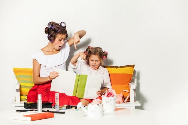 Маленькая девочка играет со своей матерью и смотрит в фотоальбом на белом Бесплатные Фотографии