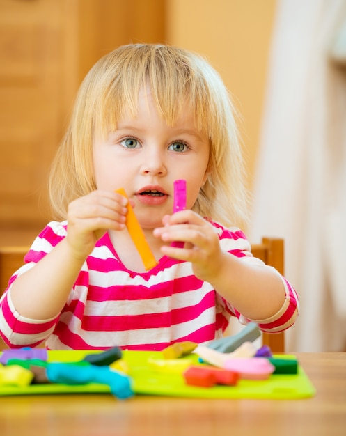 Little girl playing with plasticine Premium Photo