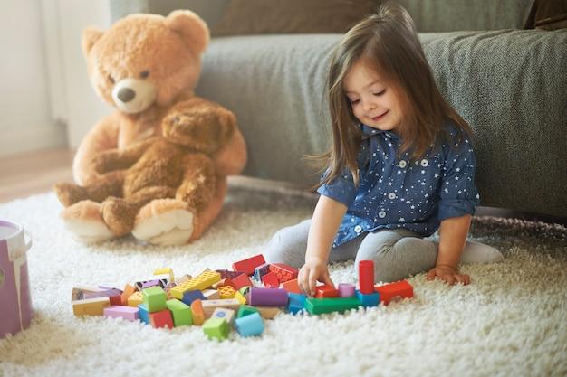거실에서 장난감을 가지고 노는 어린 소녀 무료 사진
