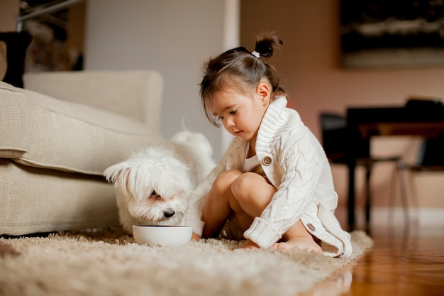 Little girl playing with white dog in the room Premium Photo