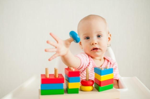 어린 소녀는 교육 장난감-멀티 컬러 나무 피라미드로 재생됩니다. 벌금 개발 프리미엄 사진