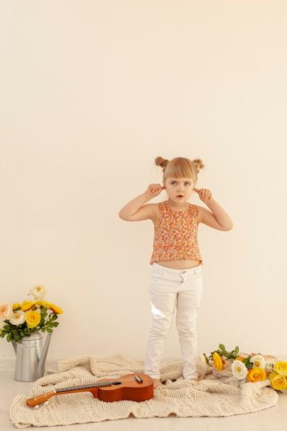 Bambina che tappa le orecchie a tutto campo Foto Gratuite
