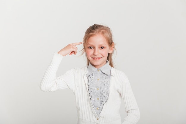 Little girl pointing towards head Free Photo