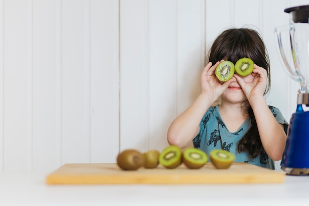 Little girl posing with kiwifruit Free Photo