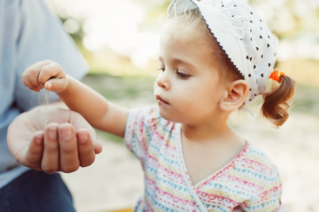 A little girl pours sand into her unrecognizable fathers hand. Premium Photo