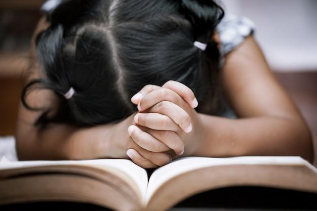 Маленькая девочка молится со святой библией Premium Фотографии