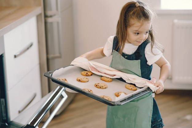 Little girl pulls a cookie tray from the oven Free Photo