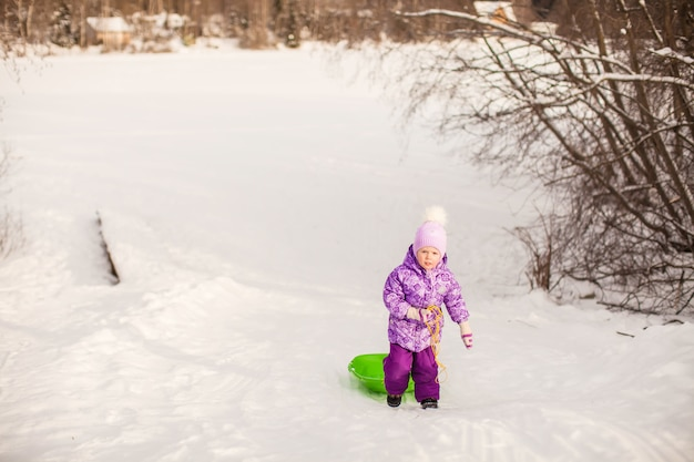 Little girl pulls a sled in warm winter day Premium Photo