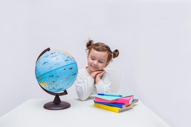 小さな女の子の瞳孔は愛情を込めて分離された白地に地球を見て Premium写真