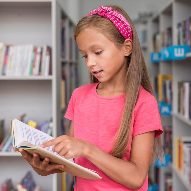 Маленькая девочка читает книгу в библиотеке Бесплатные Фотографии