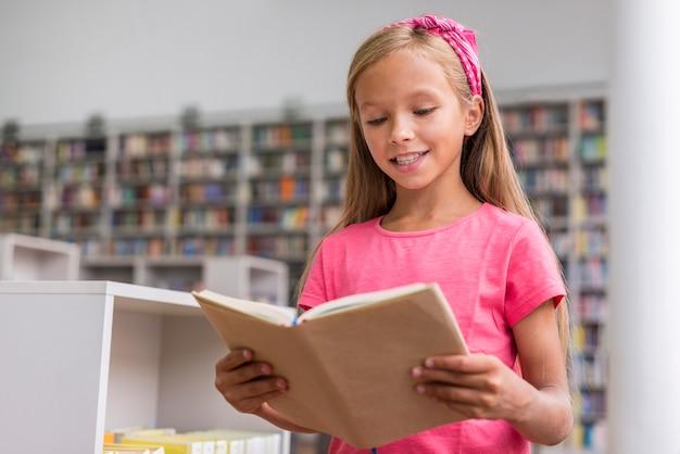 Bambina che legge un libro in biblioteca Foto Gratuite