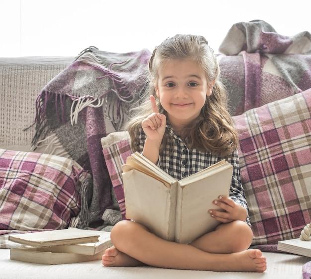 ソファで本を読む少女 無料写真