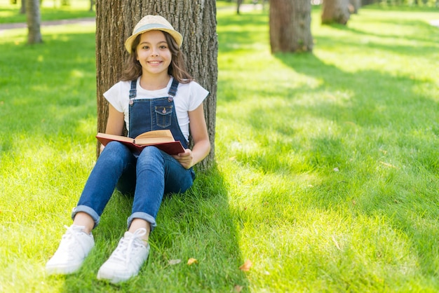 Little girl reading a book while sitting on grass Free Photo