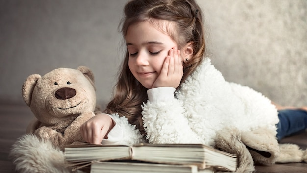 Little girl reading a book with a teddy bear on the floor, concept of relaxation and friendship Free Photo