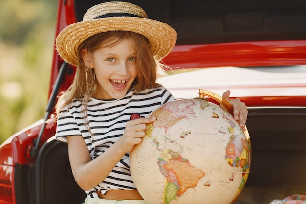 Little girl ready to go on vacations. kid in a red car. girl with globe and hat. Free Photo