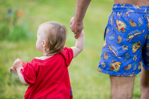 Little girl in red dress walks across the field holding father's hand Free Photo