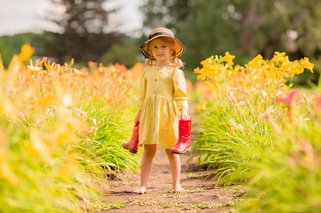 Little girl in red rubber boots and a straw hat watering red watering flowers in the garden Premium Photo