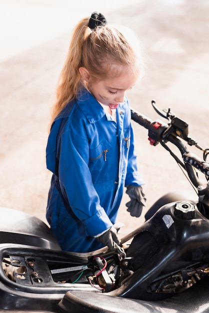 Little girl repairing  bike with spanner Free Photo