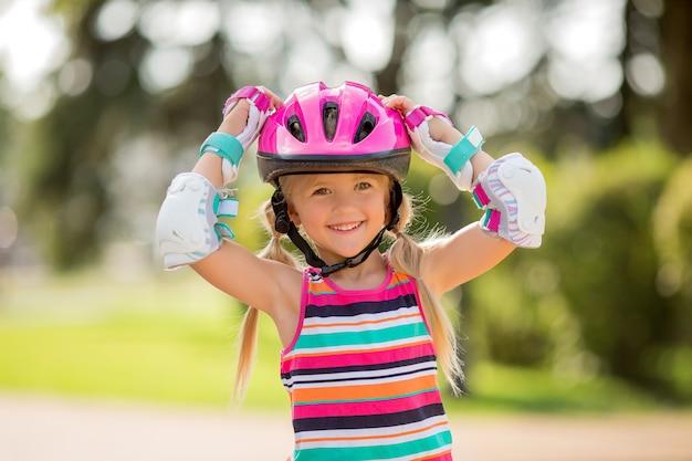 Маленькая девочка катается на роликах летом в городском парке Premium Фотографии