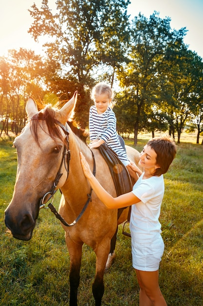 Little girl riding on a horseback with her mother standing nearb Premium Photo