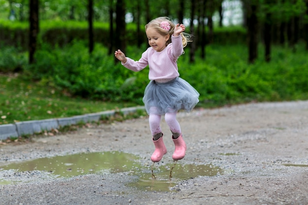 Little girl in rubber boots and tutu dress jumping in puddle. Premium Photo