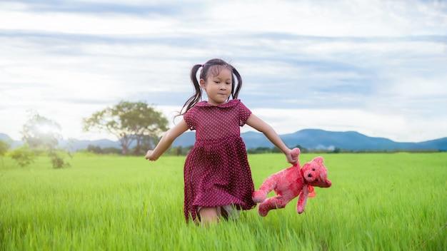 Little girl running fun in green meadows in the summer; enjoying nature Premium Photo