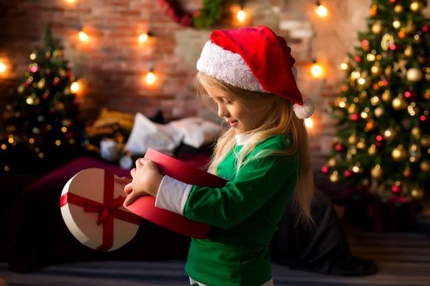 Little girl in santa hat opens a gift box Premium Photo