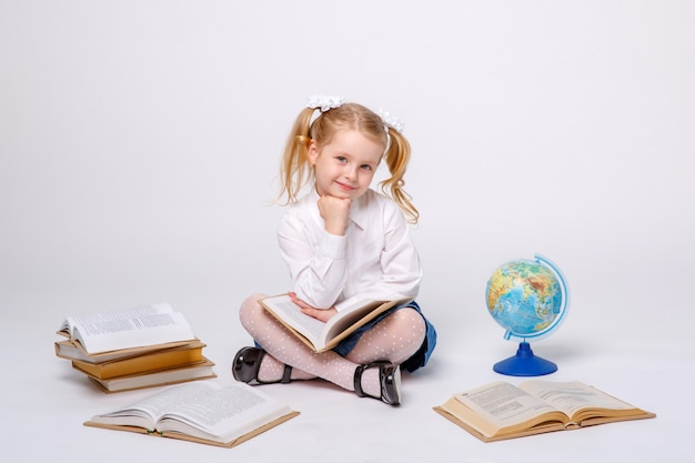 Little girl in school uniform sitting on white Premium Photo