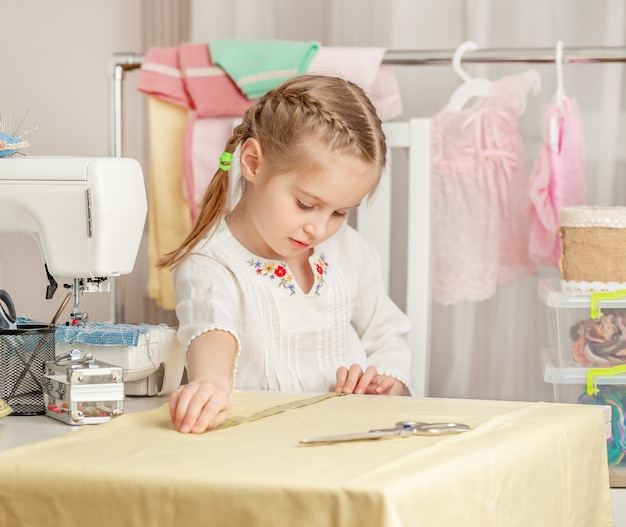 Little girl in a sewing workshop Premium Photo