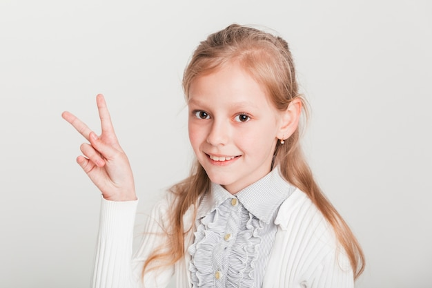 Little girl showing victory sign Free Photo