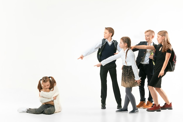 Little girl sitting alone on floor and suffering an act of bullying while children mocking. sad young schoolgirl sitting on  against white wall. Free Photo