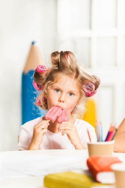 Маленькая девочка сидит и ест мороженое Бесплатные Фотографии