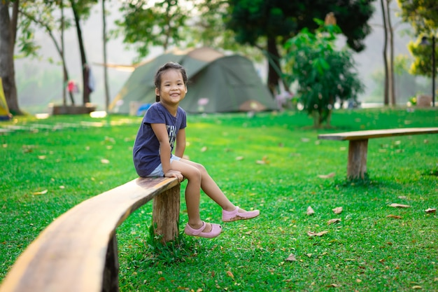 Little girl sitting on bench while going camping Premium Photo