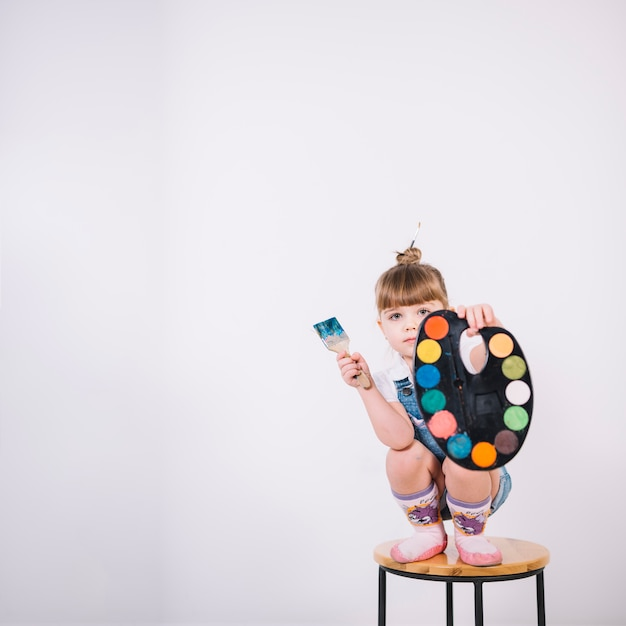 Little girl sitting on chair with palette and paint brush Free Photo