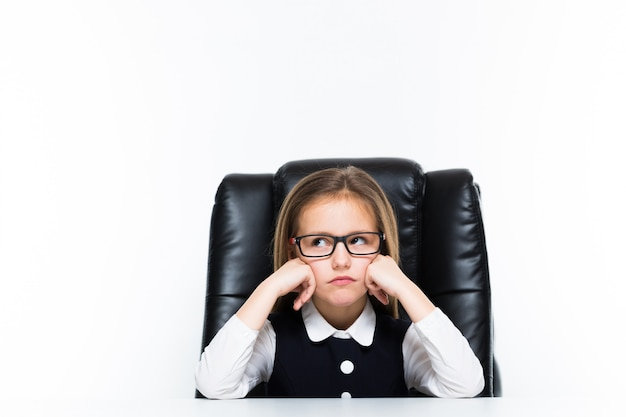 Little girl sitting on the desk at her workplace dressed as a businesswoman Premium Photo