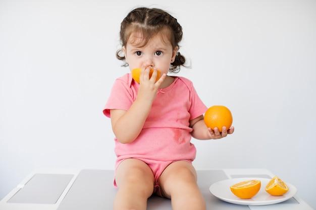 Little girl sitting and enjoying her oranges Free Photo