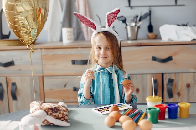 Little girl sitting in a kitchen Free Photo