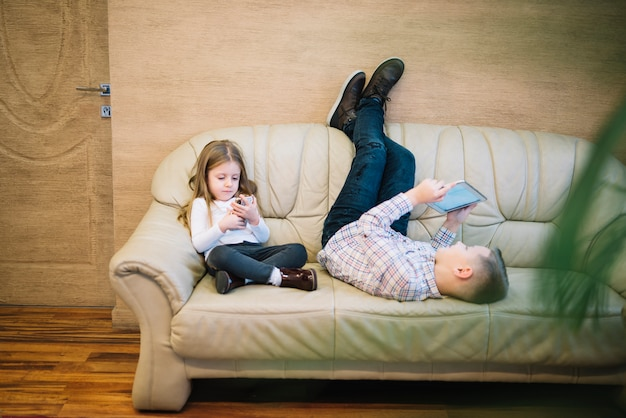 Little girl sitting near his brother looking at digital tablet on sofa at home Free Photo