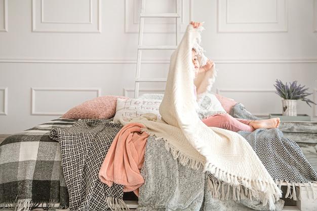 Маленькая девочка сидит на кровати с красивыми одеялами в спальне. Premium Фотографии