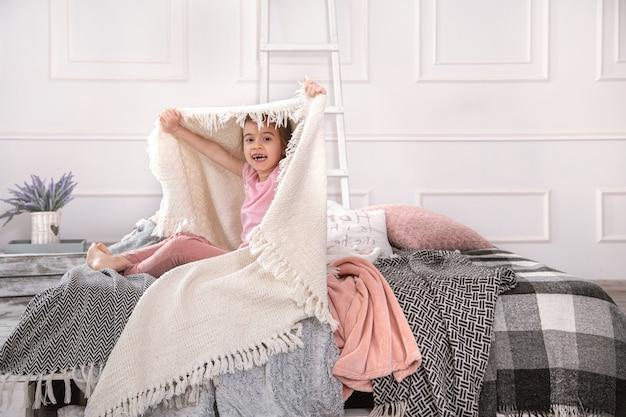 Маленькая девочка сидит на кровати с красивыми одеялами на светлом фоне спальни. Premium Фотографии