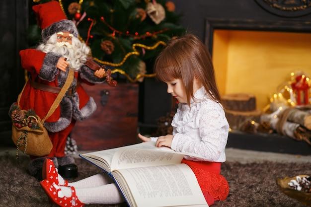 美しいクリスマスの装飾で床に座っている少女 Premium写真