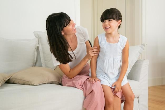 ママの膝の上に座って、笑顔でリビングルームで話している小さな女の子。 無料写真