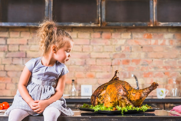 Little girl sitting on table with turkey Free Photo