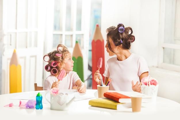 그녀의 어머니와 함께 앉아서 아이스크림을 먹는 어린 소녀 무료 사진