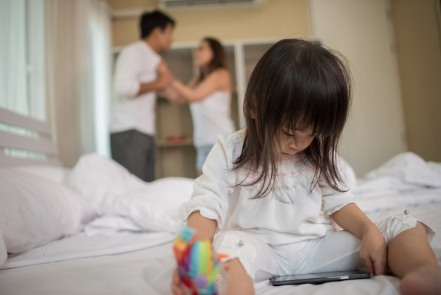 Little girl sitting with her parents on the bed looking serious Free Photo
