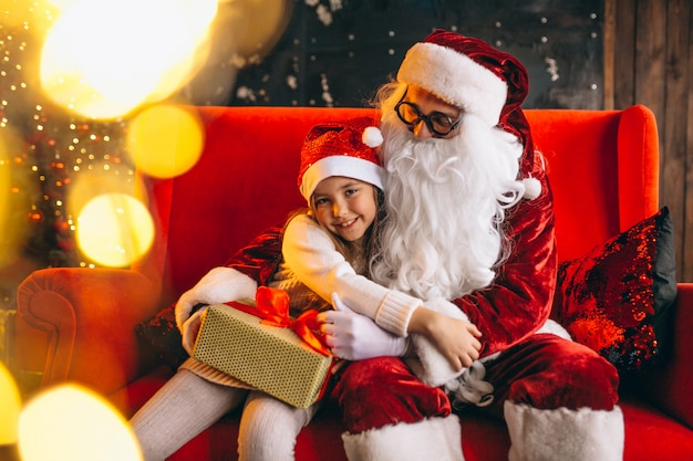 Little girl sitting with santa and presents on christmas Free Photo