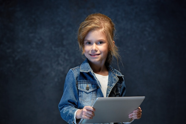 タブレットで座っている小さな女の子 無料写真