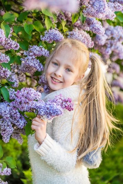 Маленькая девочка, пахнущие сиреневые цветы в солнечный день. Premium Фотографии
