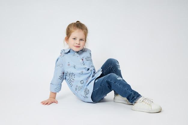 Little girl smiles. child in autumn clothes poses on white Premium Photo